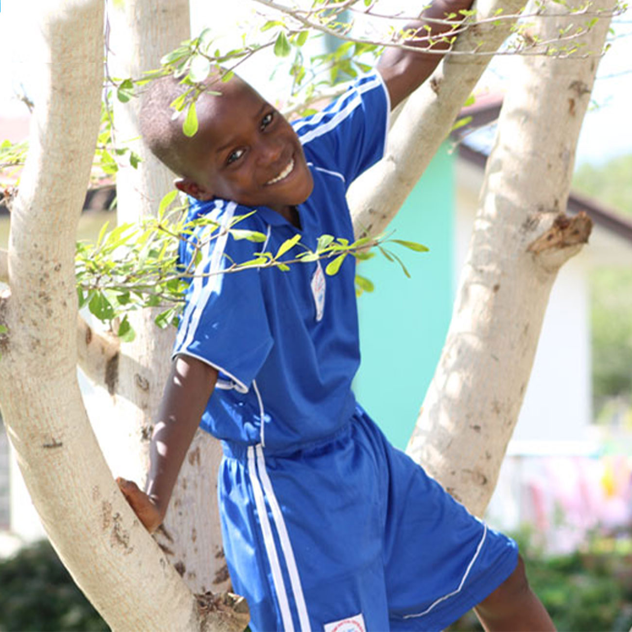 Herbalife Nutrition Foundation child smiling and climbing a tree