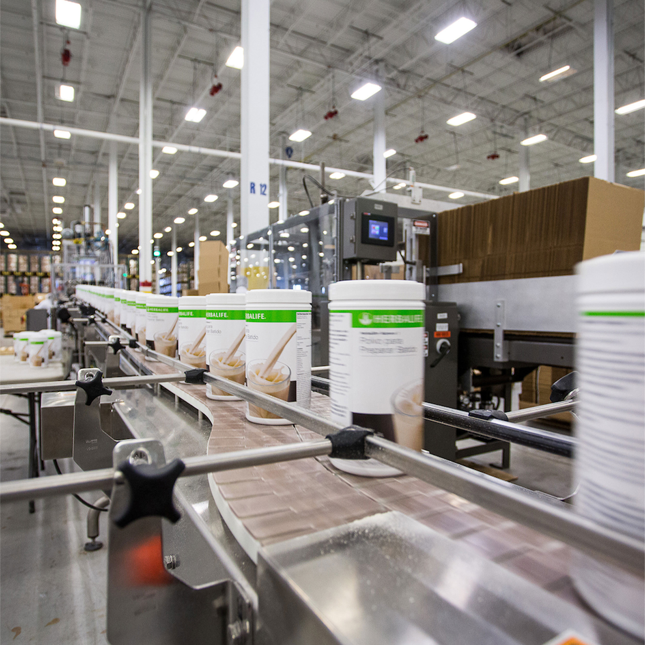herbalife nutrition factory with formula 1 canisters on the production belt